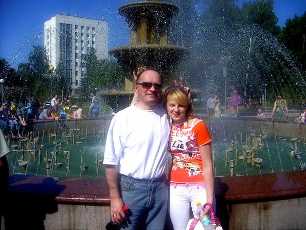 Мой муж и дочь в Городском парке на площади Новособорной. На заднем фоне здание областного Статуправления на улице Гагарина