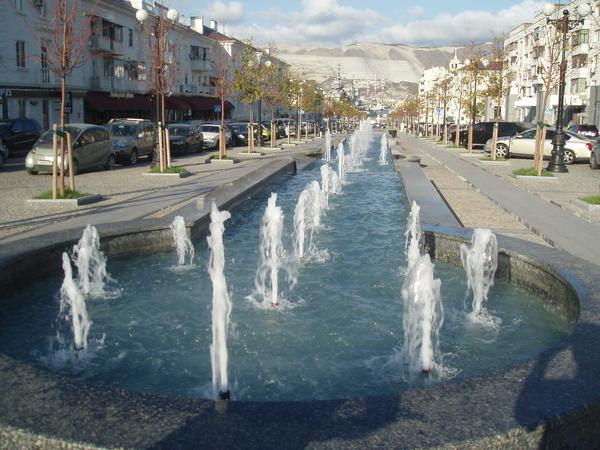 Ул. Новороссийской республики, по обе стороны от фонтана расположены тротуары, ведущие к Морскому вокзалу