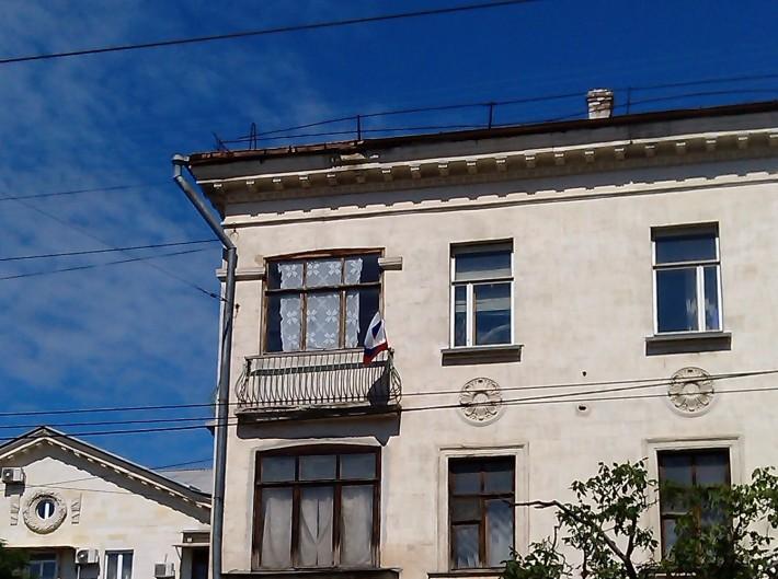 Жители с балконов вывешивают флаги России