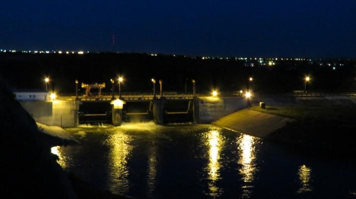 На фото плотина и огни ночного города