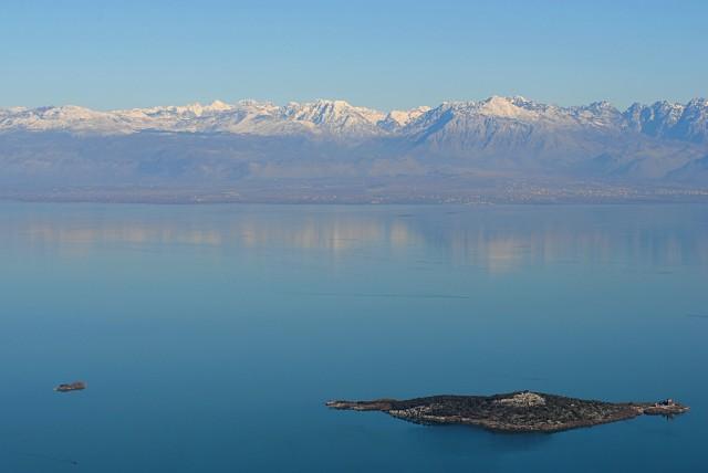 Трудно жить среди такой фантастической красоты и не верить в бога. На снимке: Скадарское озеро и черногорские острова с монастырём на одном из них. На том берегу — албанский город Шкодер (Скадар)