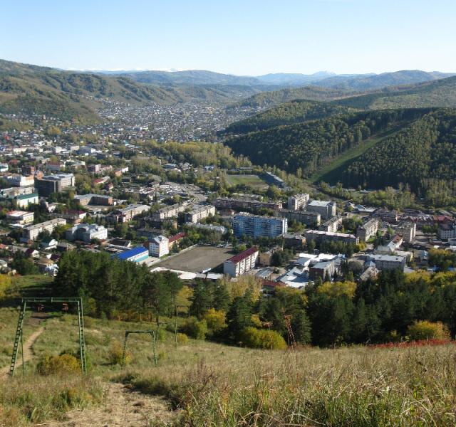 Вид с горнолыжного спуска горы Тугая на город и горнолыжный спуск на горе Комсомолка