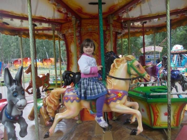 Дочка на аттракционе в парке