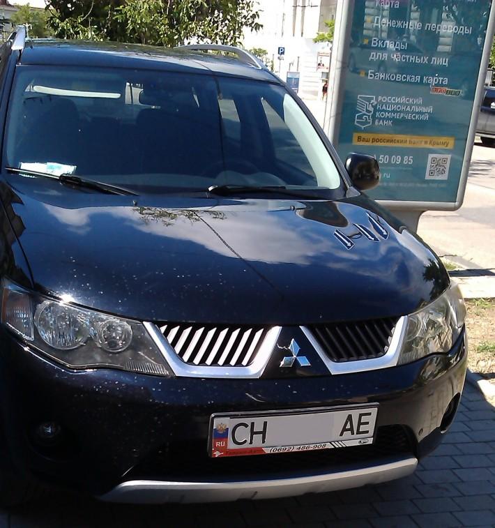 Автомобиль на севастопольских номерах с наклеенным флагом России